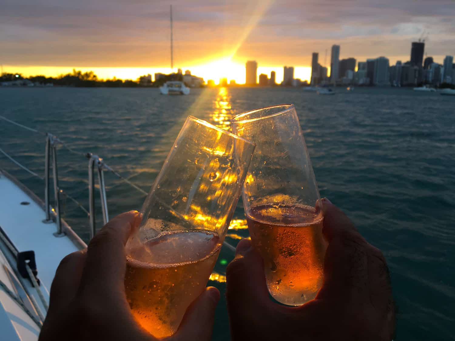 couple celebrating creating their luxury crewed charter business with champagne after working with catamaran guru